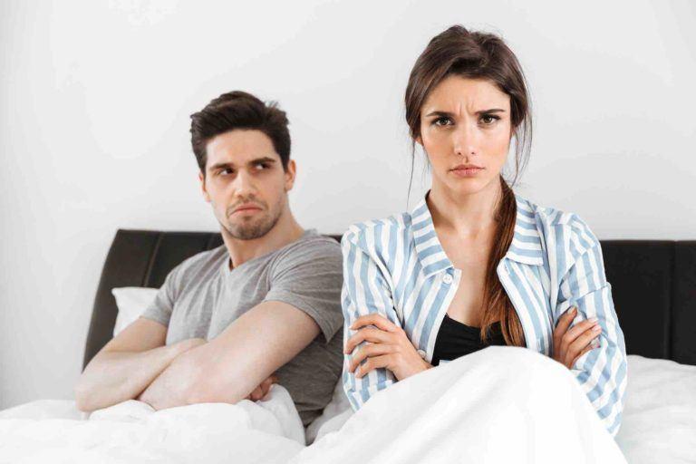 Frau sitzt mit verschränkten Armen im Bett