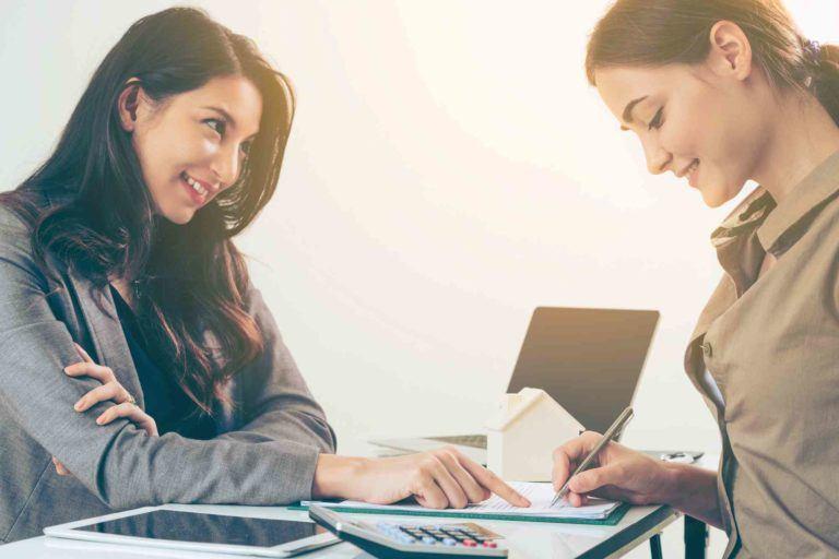 Frau unterzeichnet ein Dokument bei einer Anwältin