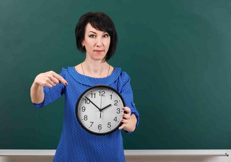 Frau zeigt mit Zeigefinger auf die Uhr