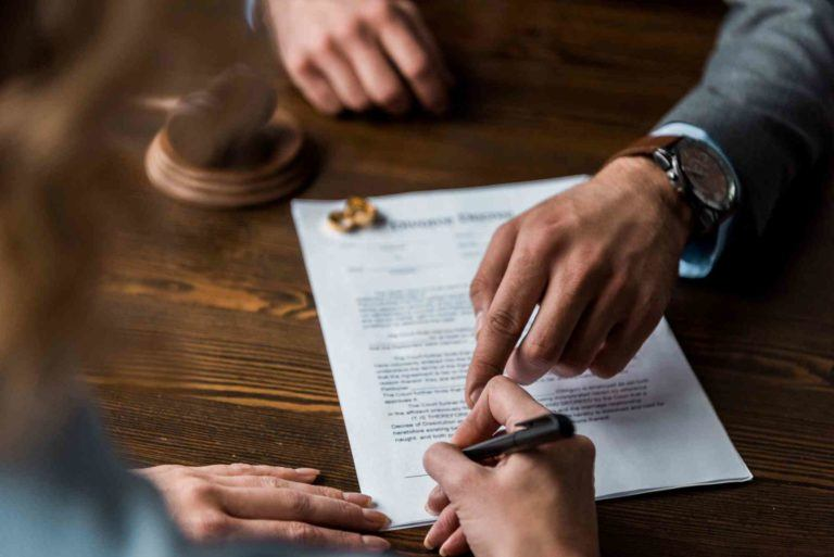 Anwalt zeigt auf Papier, Mandant untrschreibt