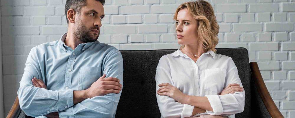 Ehepaar in Trennung sitz mit verschränkten Armen nebeneinander