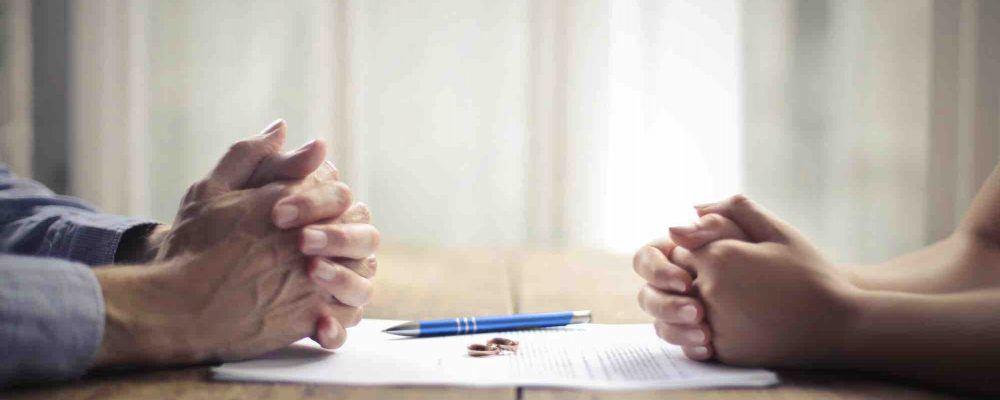 Frau und Mann sitzen mit verschränkten Händen gegenüber