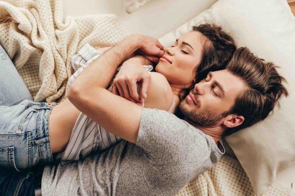 Paar liegt umarmt im Bett