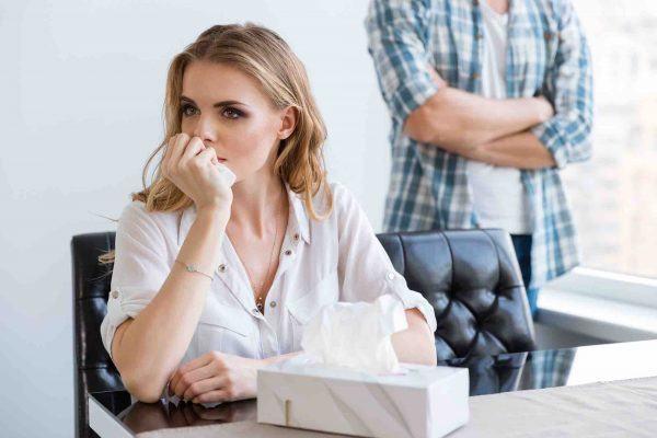 Frau sitzt mit Taschentüchern vor Mann