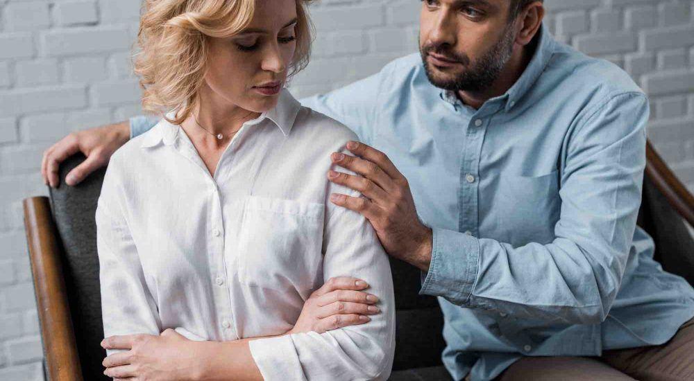 Ehepaar legt Hand auf die Schulter der Frau