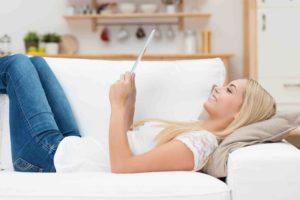 Frau liegt mit Tablet am Sofa