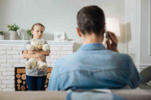 Vater telefoniert am Sofa und Tochter steht mit Kiuscheltier davor